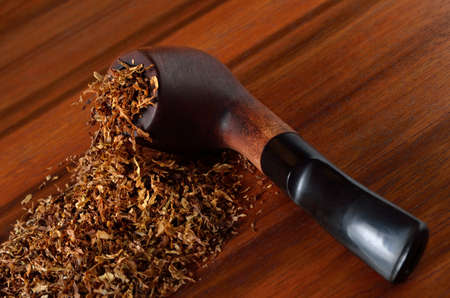 Tobacco accessories, smoking pipe and tobacco close-up.