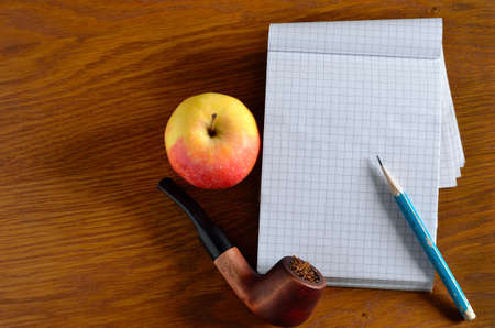 Apple, diary, pencil and smoking pipe on the wooden desktop 免版税图像 - 161756840