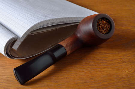 Smoking pipe and workbook on the wooden desktop