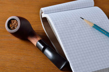 Notebook, pencil and smoking pipe on the wooden desktop