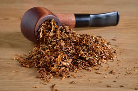 Wooden smoking pipe and tobacco close-up. 免版税图像