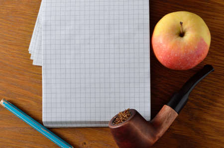Apple, diary, pencil and smoking pipe on the wooden desktop