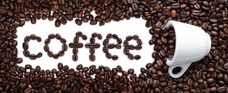 Coffee word and cup among roasted coffee beans