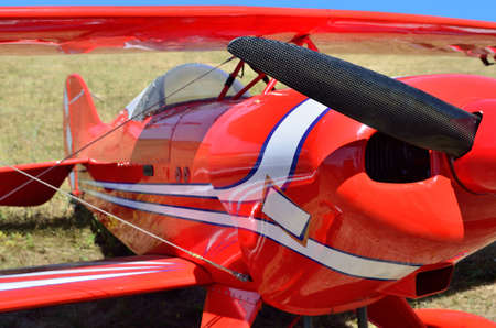 Red plane stands on a dirt runway