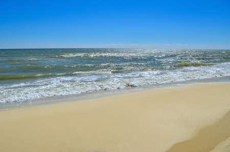 Sea waves wash the beach against a blue sky. Landscape on a wild beach.
