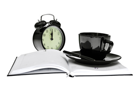 jot: Agenda with pen and coffe on top and clock behine, office tools for doing business Stock Photo