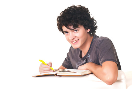 Young college student holding pen in his hand, writing in agenda.