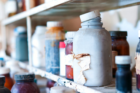 Old chemical containers on a shelf, colored and vintage feeling. Stock Photo