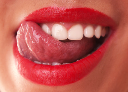 Young Woman with red lips licking teeth laughing with mouth opened.