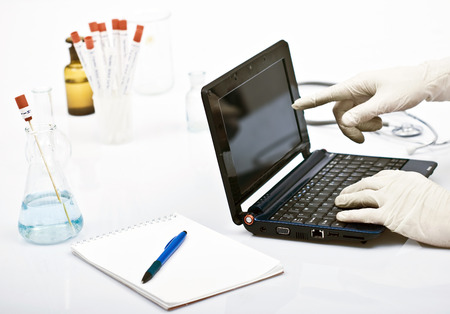 chemist in laborator with laptop in front, pointing to research