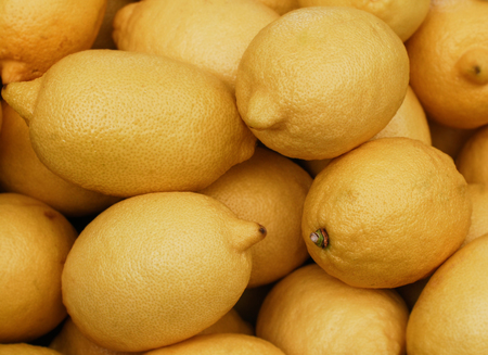 Pile of lemons, with focus on the lemons that are above.