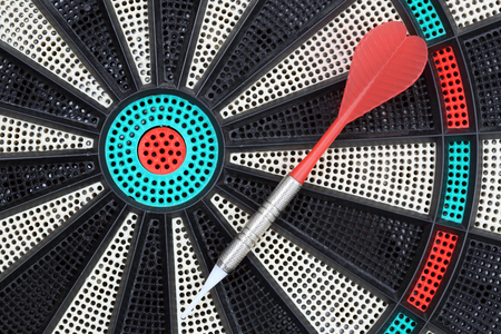 Darts gameboard and colored arrow on top. Stock Photo