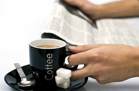 Drinking coffee in short break at office and reading newspaper Stock Photo