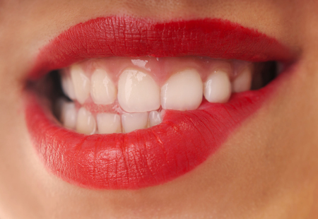 Woman with red lipstick biting her lip.