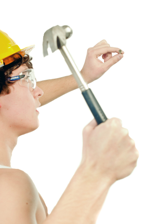 Worker equiped with crash-helmet and goggles holding hammer, nailing a nail, on white background. Stock Photo
