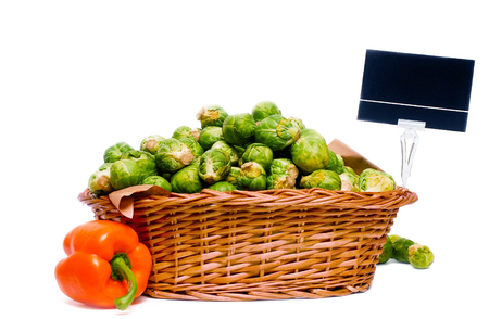 Wooden basket full of brussels sprouts and a orange capsicum on the side, for market use, isolated on whte with price tag.