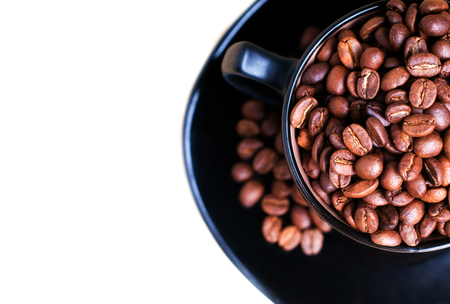 Coffee mug full of coffee beans and white background.