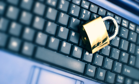 Laptop keyboard with locker and keys on top. Stock Photo