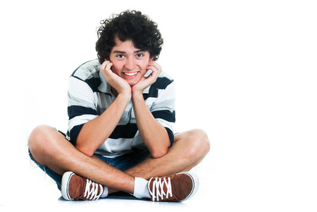 Young adult sitting on the floor, looking at the camera, on white background. Stock Photo