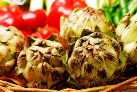 Basket full of artichoke, on a table full of vegetables at the market