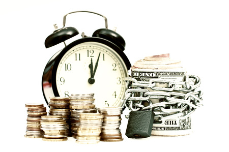 Time and money concept with coins and banknotes rapped in chains and clock in the background, all isolated on white, old style