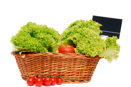 Wooden basket full of lettuce and a some small tomatoes, for market use, isolated on white.