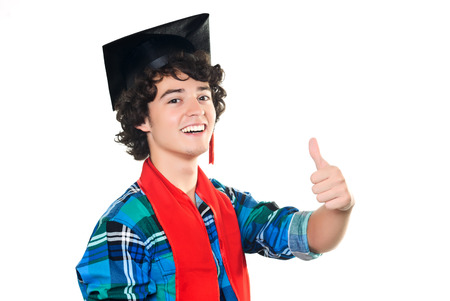 Young student dressed in casual clothes wearing the graduation hat and a red scarf smiling at the camera and showing the Ok sign with his left hand, on white background. Stock Photo