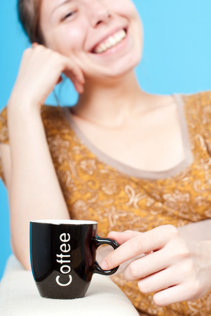 Woman relaxing on a couch holding a  cup of coffee j. Cup of coffee in focus and a woman out of focus sitting on the couch.