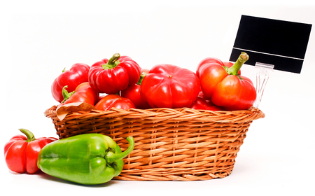 Wooden basket full of red capiscum and a green capsicum on the side, for market use, isolated on whte.