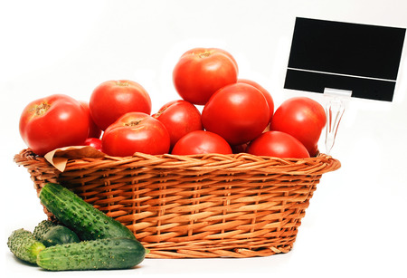 Wooden basket full of tomatoes and some cucumber on the side, for market use, isolated on whte.