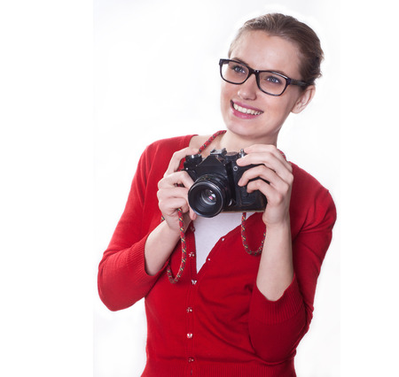 Young girl with bi smile posing as a photographer holding vintage camera, on white background.