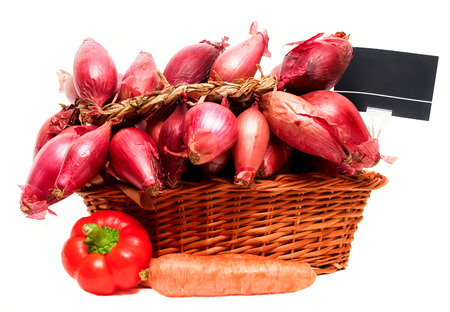 Basket full of red onions and price tag, isolated on white background.