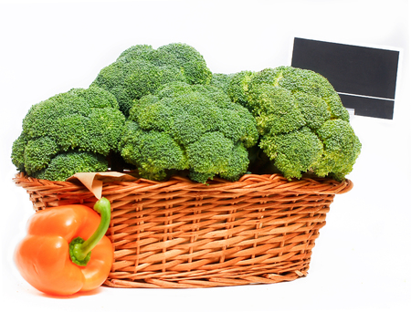 Basket full or red broccoli and price tag, isolated on white background.