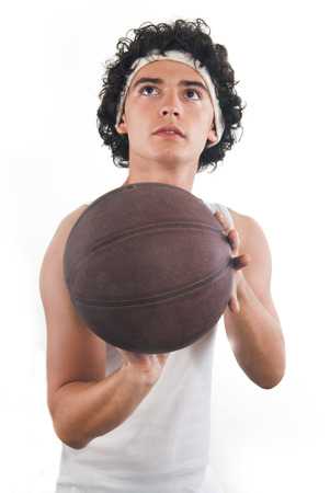 Teenager holding basket ball, ready to throw the ball on white background.