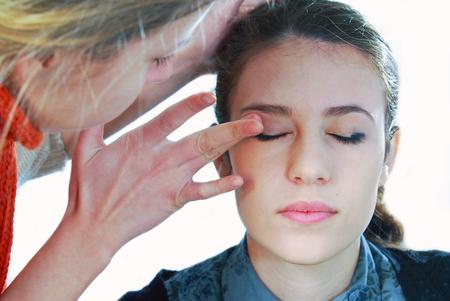 Make-up artist applying foundation cream on model.