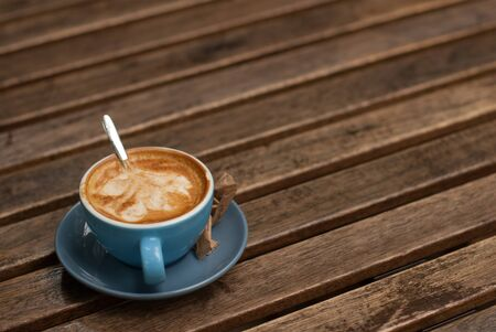 Blue cup of coffee filled with creamy espresso on a wodden table.