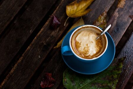 Blue coffee cup filled with coffee and cream on top, on a autumn rainy brackground with wooden table and leaves Stock fotó