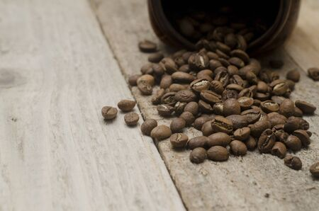 Pile of coffee beans spilled on a wooden table
