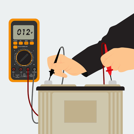 The man appliance measures the battery voltage. Machine battery and multimeter.