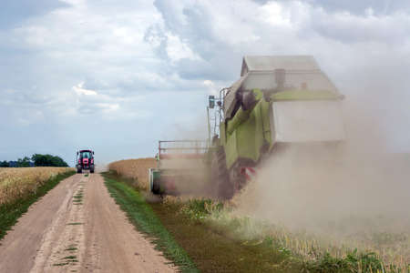 The combine harvester rape, and the tractor goes to unload it.