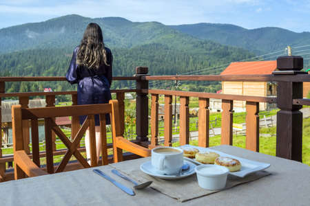 A young woman enjoys a mountain landscape while her breakfast is cooling down.