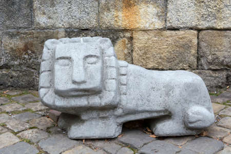 ancient stone sculpture of a lion with a square head. Imagens