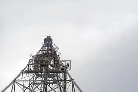 TV tower with telephone transmitters against a cloudy sky. Banco de Imagens