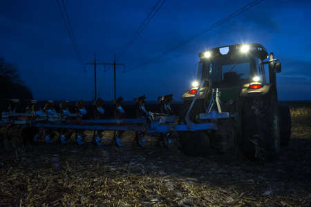 two tractor plowing the land late at night with the headlights on.
