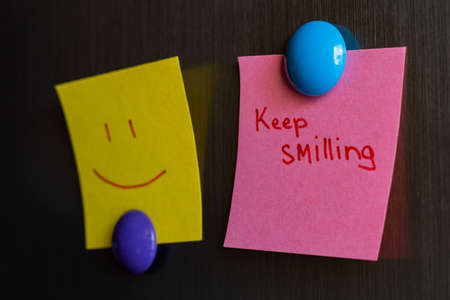 sticky notes keep smiling and smiley magnet attached to the refrigerator