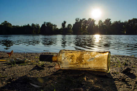 old glass bottle by the river. water pollution concept. 写真素材