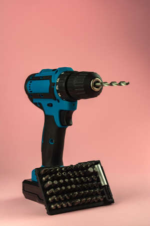 electric drill with a drill on a pink background.