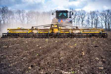 tillage in the field with a tractor with a trailed machine.