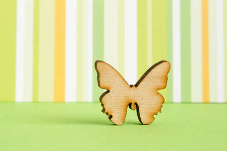 Wooden icon of butterfly on green striped background horizontal photo