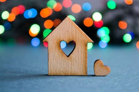 case colorate: Casa di legno con il foro a forma di cuore con poco cuore su sfondo colorato bokeh.